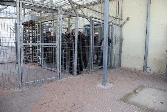 分離の壁の検問所で通過の許可を待つパレスチナ人