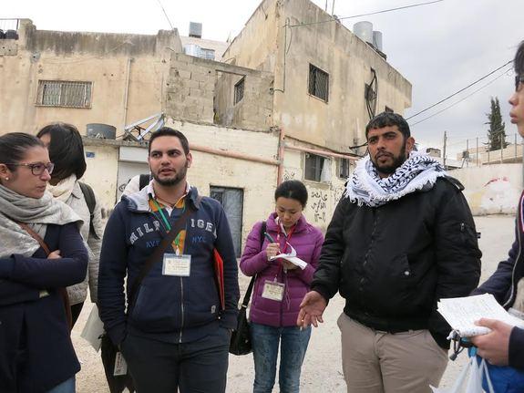 現地の状況を説明するパレスチナ人のスタッフ